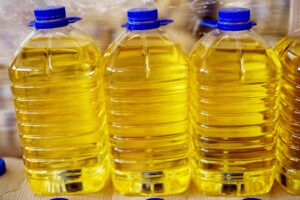 vegetable seed oils 300x200 - Close up view of three big transparent plastic bottles with blue