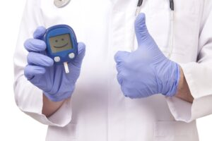 reversing managing diabetes on low carbs 300x200 - Doctor holding blood sugar meter. Showing OK sign