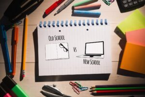 old school new school 300x200 - old school vs new school  against students table with school supplies